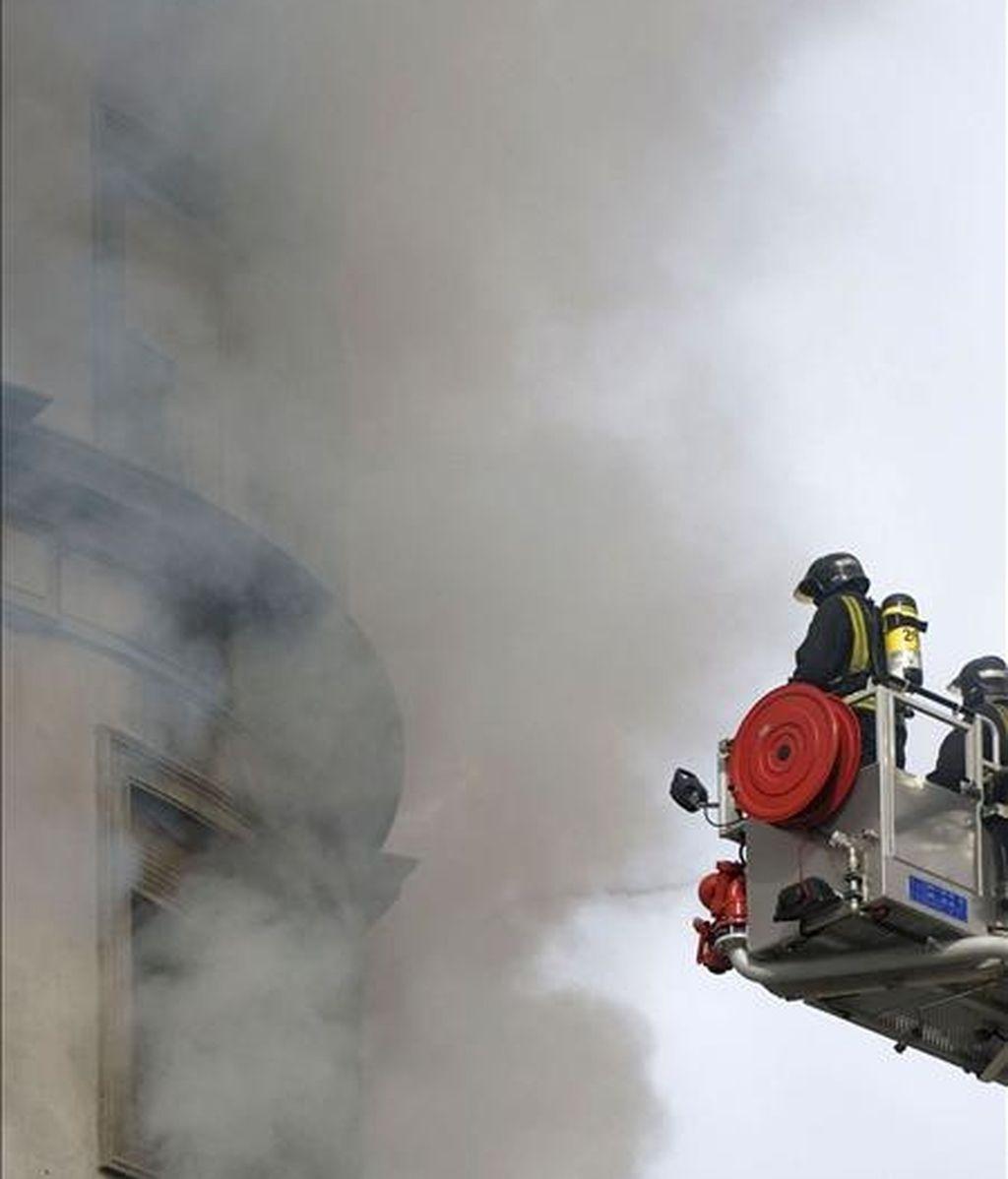 Unos bomberos trabajan en el control y extinción del incendio que se ha declarado esta mañana por causas desconocidas en una vivienda situada en la esquina de la plaza de América de Valencia con la calle de Cirilo Amorós. EFE