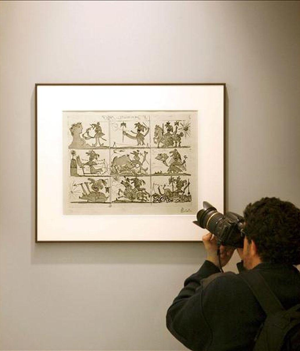 """Un fotógrafo toma una imagen de uno de los cuadros que componen la exposición """"Sueño y mentira de Franco"""", del pintor Pablo Picasso, que desde hoy y hasta el próximo 3 de mayo se podrá visitar en la Casa Museo Casares Quiroga, antigua residencia coruñesa del presidente de la República, Casares Quiroga. EFE"""