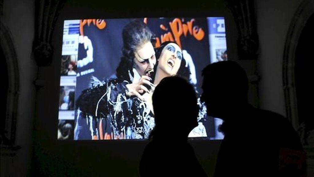 """Dos personas se besan ante una de las imágenes que forman parte de """"Besos"""", una producción de EFE Televisión con fotografías de los reporteros de la Agencia. EFE"""