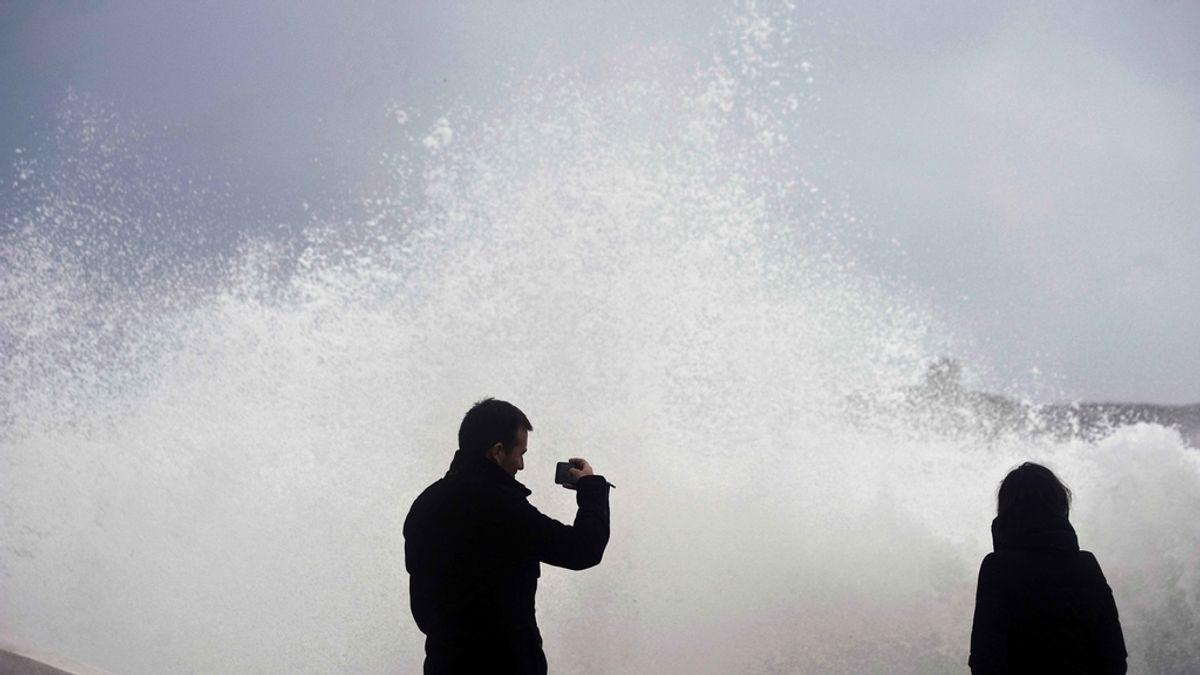 Dos personas en S'Algar en el municipio de Sant LLuís, Menorca, donde se registra un fuerte oleaje