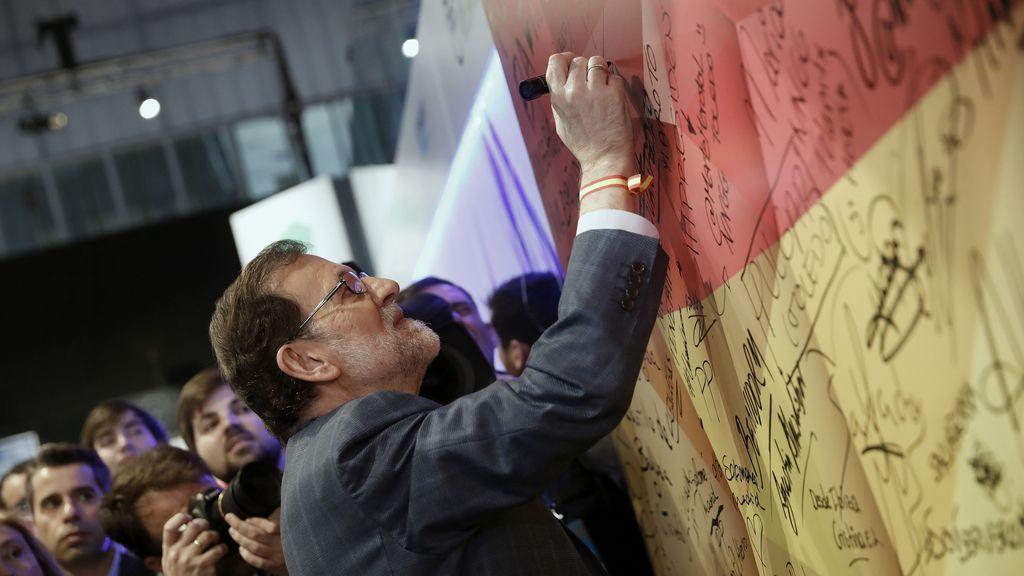 Mariano Rajoy firma en una bandera de España