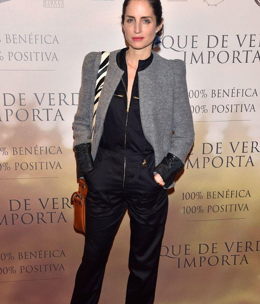 Carolina Adriana Herrera, con mono negro satinado y bolso estampado