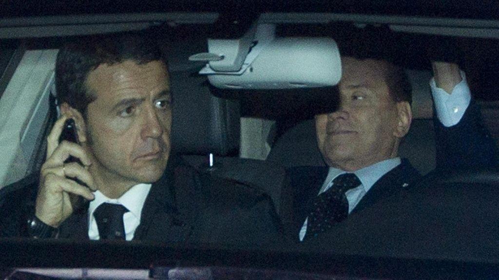 El primer ministro italiano Silvio Berlusconi saluda desde el interior del vehículo en el que se traslada al palacio presidencial, para presentar formalmente su dimisión al presidente de la república, Giorgio Napolitano, en Roma, Italia.