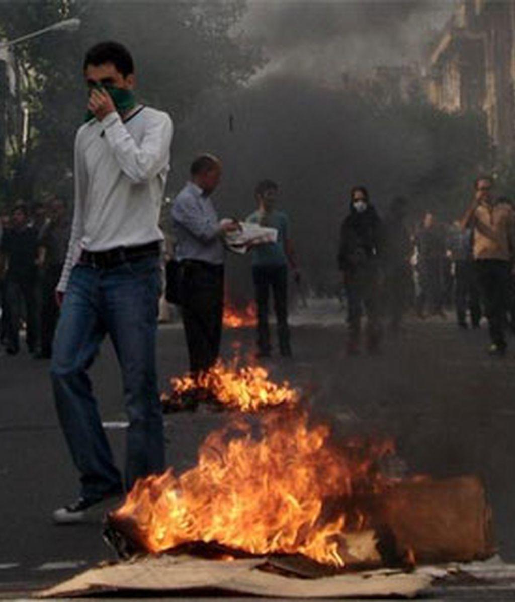 Un manifestante en medio del humo y el fuego provocado tras las protestas de la oposición en Teherán. Foto: EFE
