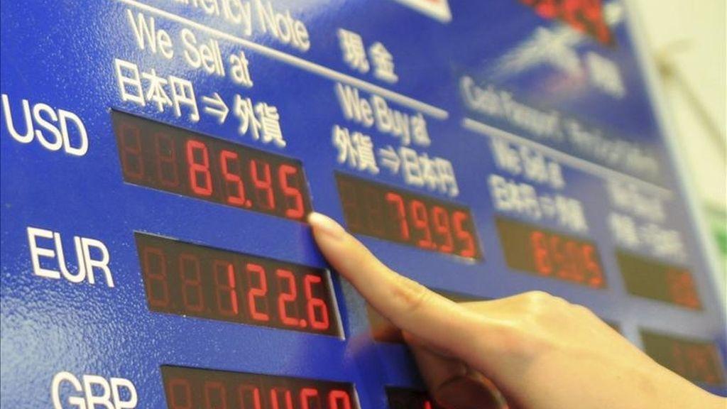 Una mujer observa una pantalla en una casa de cambio en Tokio, Japón. La Bolsa de Tokio bajó en su apertura 62,53 puntos, el 0,65 por ciento. EFE/Archivo