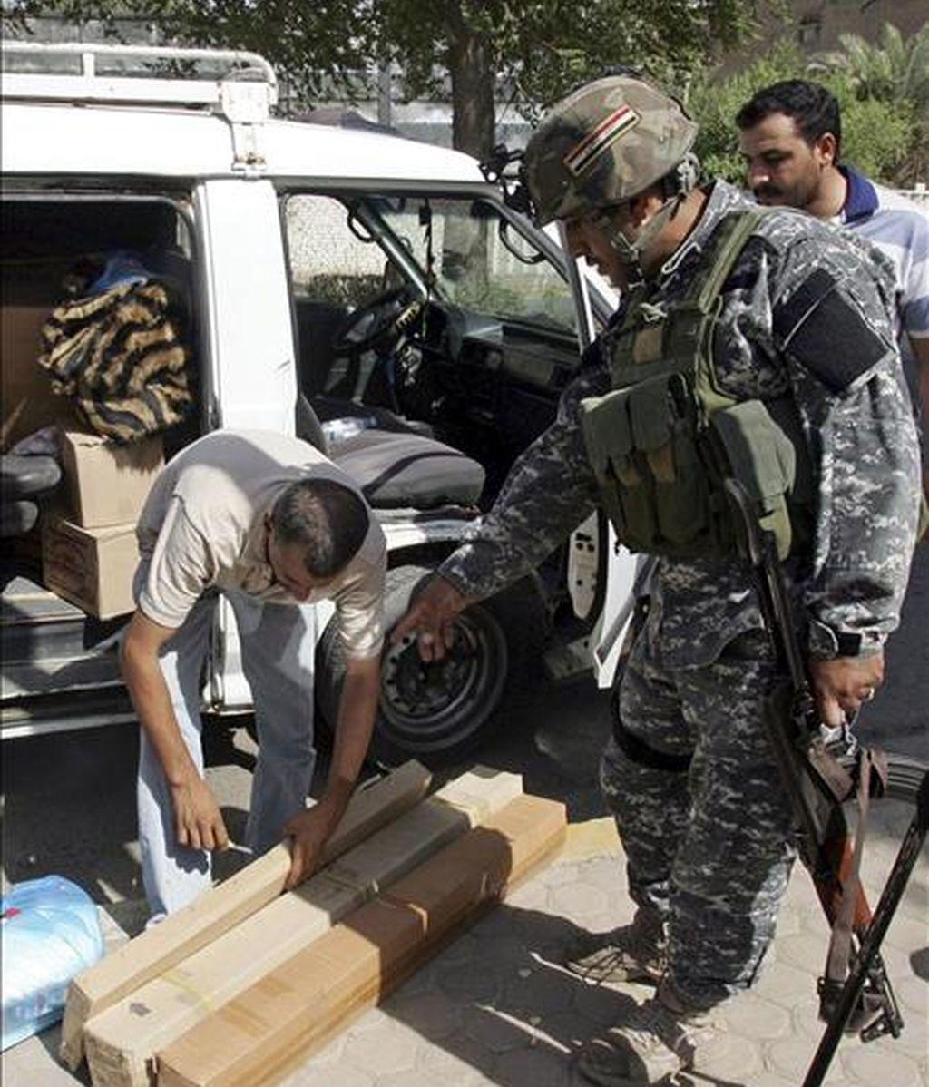 Un policía iraquí inspecciona hoy la mercancia de un vehículo en un punto de control del centro de Bagdad, Irak. EFE