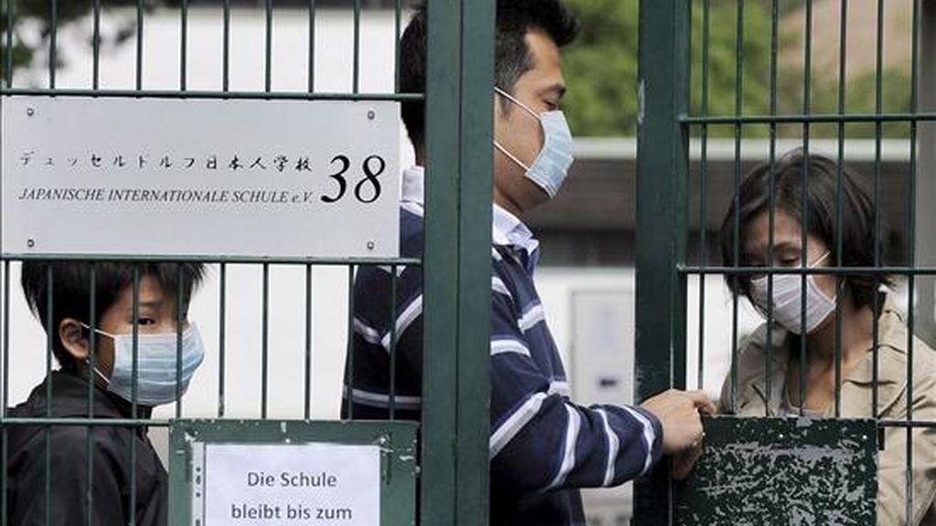 Varias personas con máscaras abandonan el Colegio Internacional Japonés, que permanecerá cerrado hasta el próximo 19 de junio, en la localidad alemana de Dúseldorf hoy, viernes 12 de junio. El número de alumnos infectados con el virus de la gripe A en este centro subió ayer a 32, según informaron las autoridades sanitarias de esta ciudad alemana. EFE
