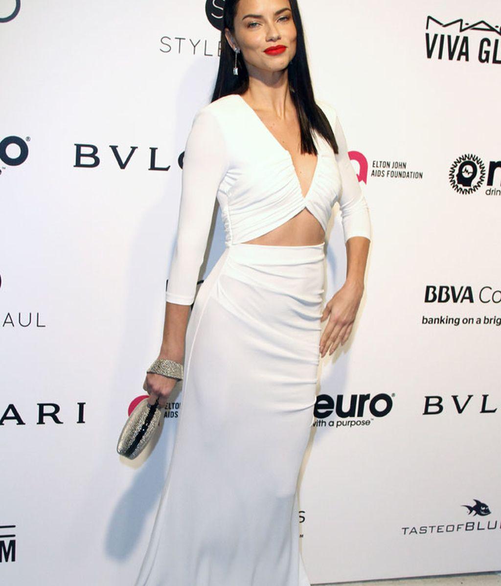 Adriana Lima con un vestido blanco con aberturas y complementos en plata