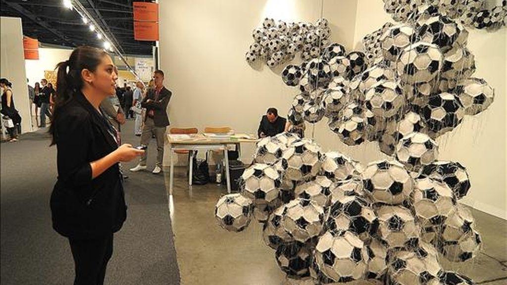 """Una mujer observa la instalación conceptual """"Obverse & Reverse"""" del guatemalteco Darío Escobar, hecha a base de pelotas de fútbol cosidas unas con otras durante un previo a la inaguración de la prestigiosa Art Basel Miami Beach. EFE/Archivo"""