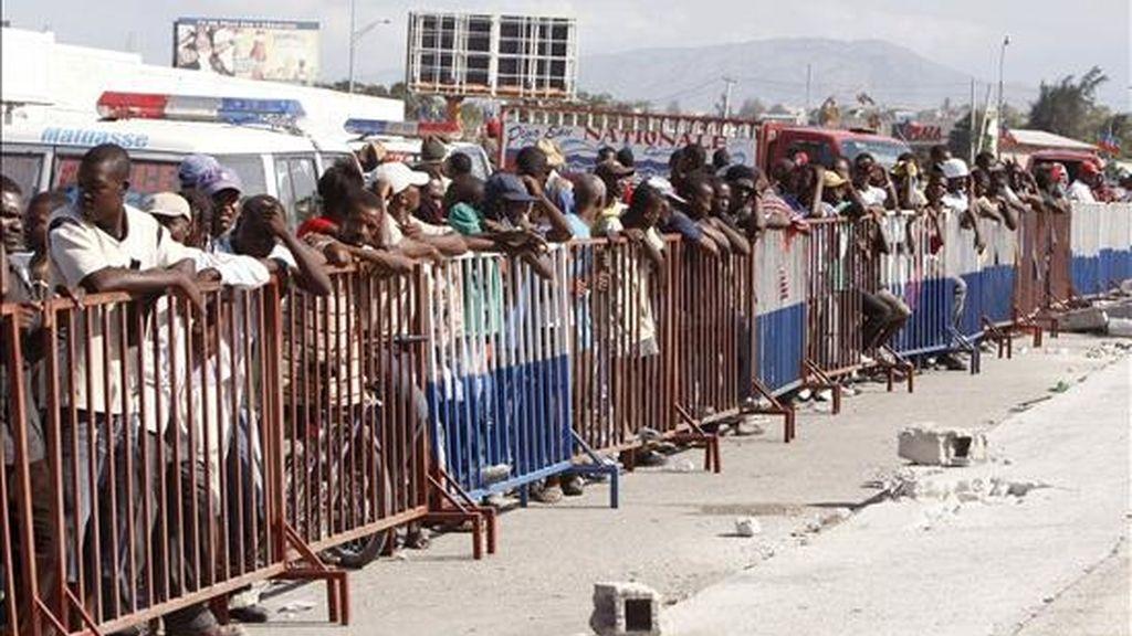 Varias personas esperan en la zona de entrega de alimentos y agua, en las inmediaciones del parque insdustrial de Puerto Príncipe (Haití). EFE/Archivo