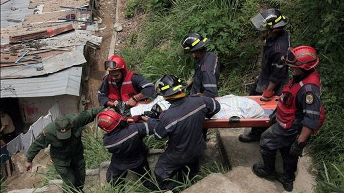 Un grupo de socorristas rescata el cuerpo de uno de los cinco de siete miembros de una misma familia que murieron sepultados tras un deslizamiento de tierra y rocas que afectó a su vivienda en una barriada popular aledaña a Caracas (Venezuela). EFE