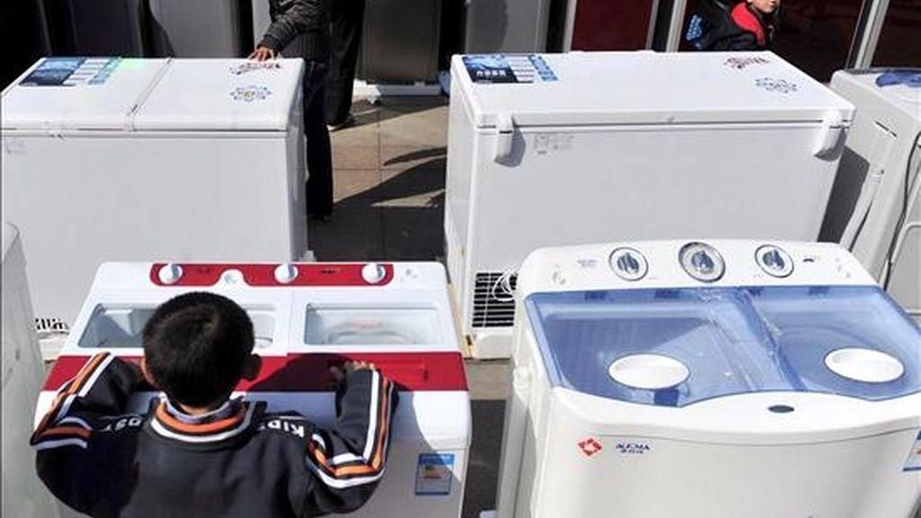 Un niño observa una lavadora en un almacén de venta de electrodomésticos. EFE/Archivo