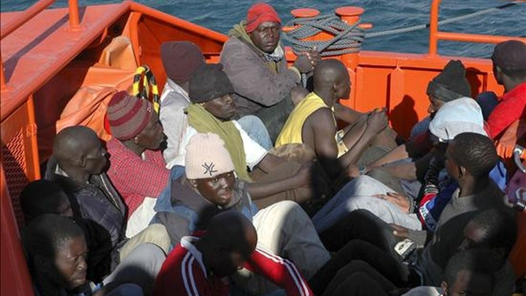 Los entre 70 y 80 inmigrantes africanos que viajaban a bordo de un cayuco que fue avistado a milla y media del Faro de Maspalomas, al sur de Gran Canaria, hoy en su traslado al Muelle de Arguineguín, en el municipio de Mogán. EFE