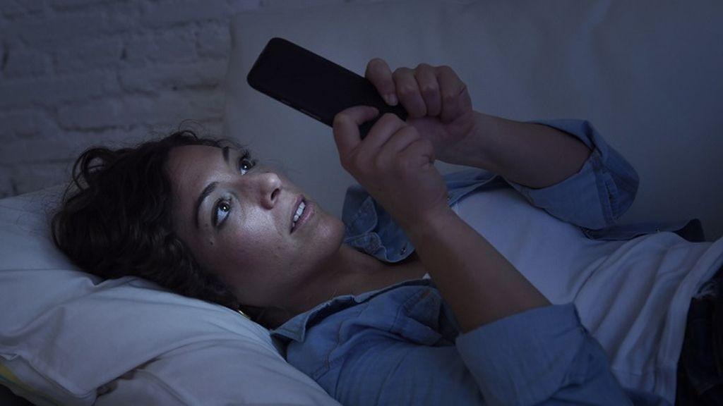 Imagen de una mujer viendo el teléfono móvil