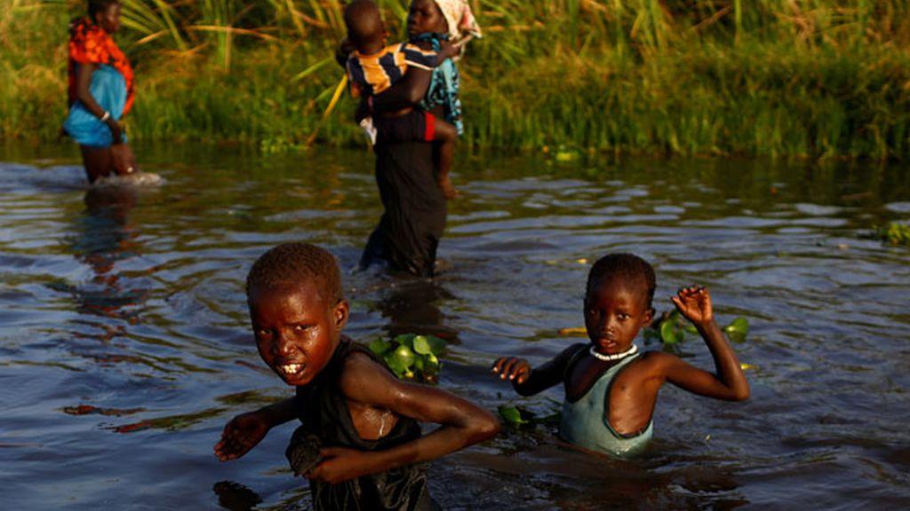 Niños en Sudán el Sur, cruzan el río para llegar al registro de suministro de comida de la ONU
