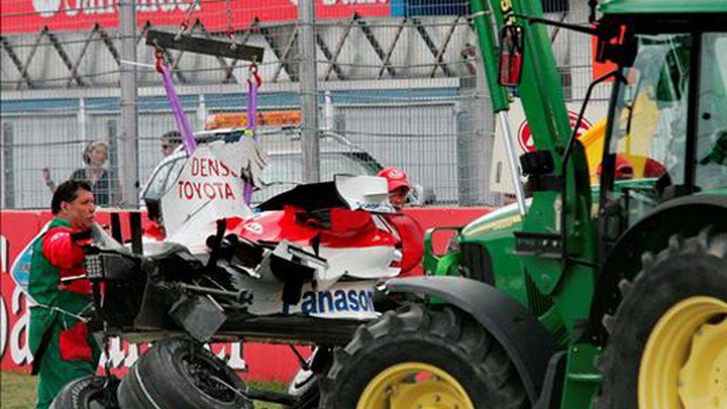El destruido coche del piloto alemán Timo Glock (Toyota) es recogido por una grúa tras accidentarse durante el Gran Premio de Alemania