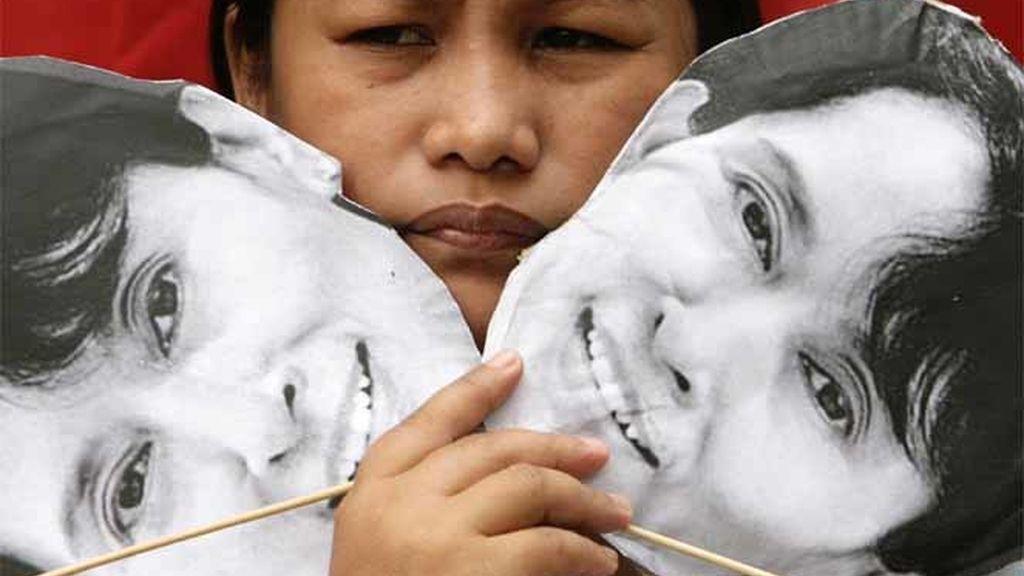 Un manifestante sostiene dos imágenes de Aung San Suu Kyi durante una protesta ante la embajada de Myanmar en Manila