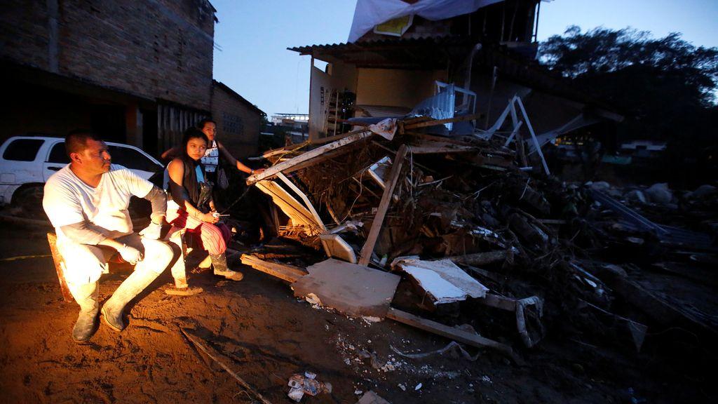 Una familia permanece sentada fuera de su casa tras ser destruida por las fuertes lluvias