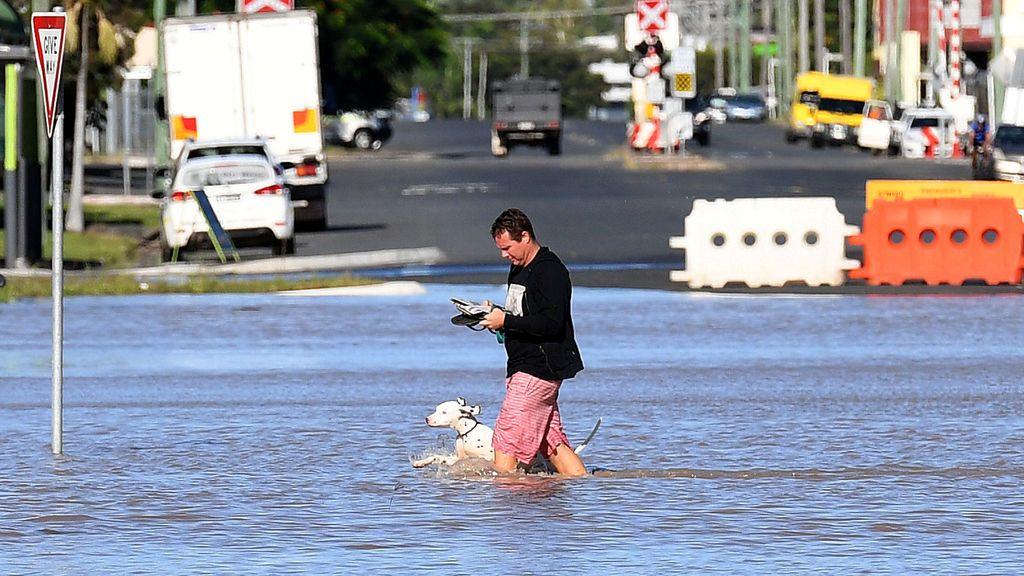Un hombre y su perro camina por una calle anegada en Rockhampton