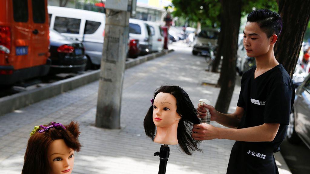 Un peluquero prepara sus pelucas en plena calle de Pekín