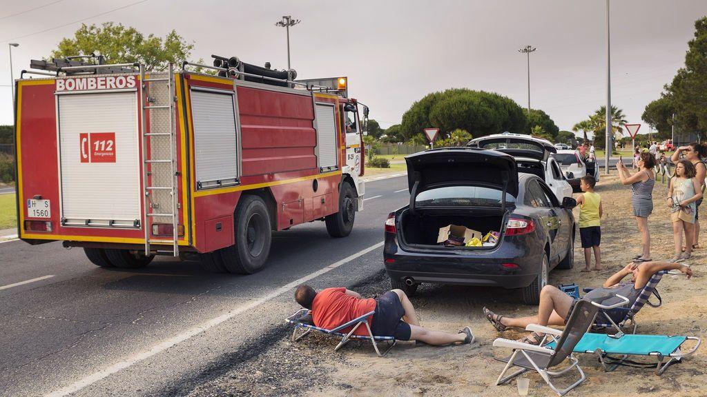 Varios turistas esperan a que abran la carreteras de salida desde Matalascañas, cortadas por el incendio de Moguer que se extiende por Doñana, para volver a sus casas.