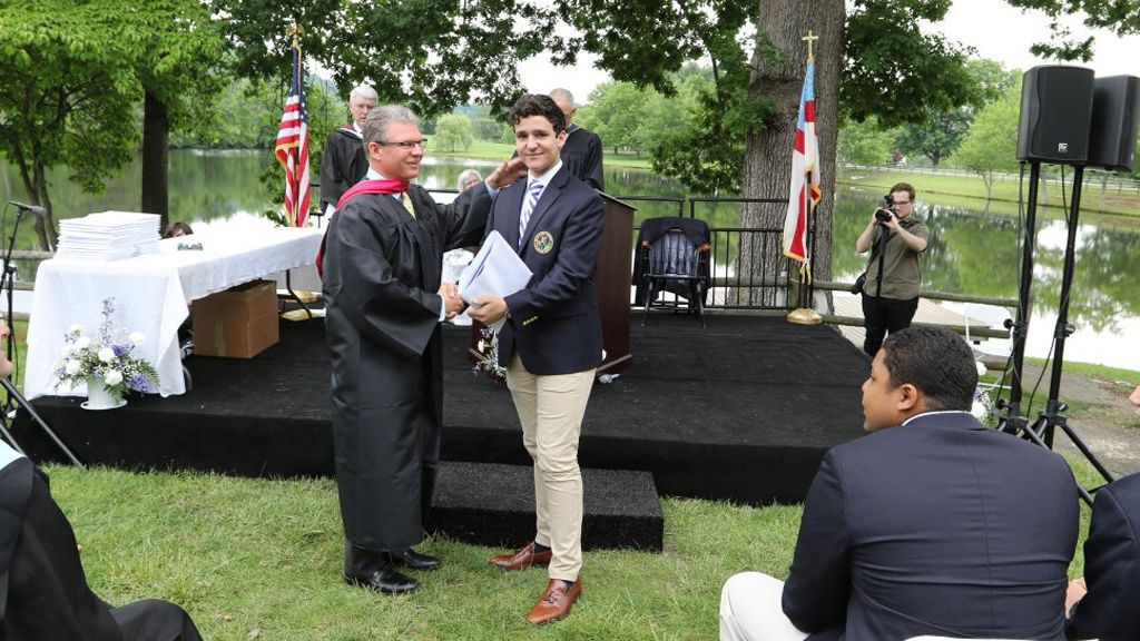 El hijo de la infanta Elena mientras recibe el diploma de graduación.