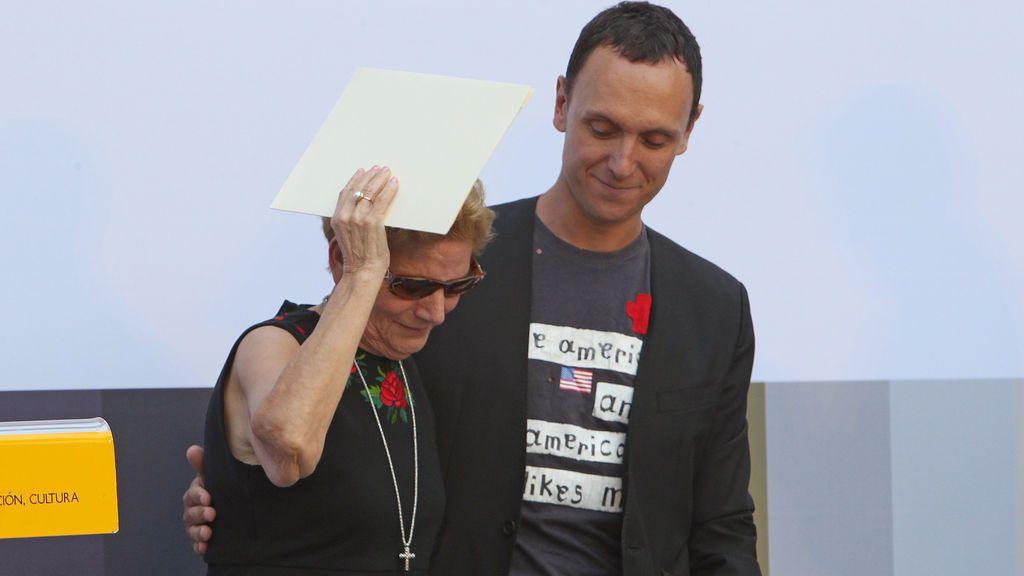 La madre de David Delfín recogiendo el Premio Nacional de Diseño de su hijo al lado de Gorka Postigo