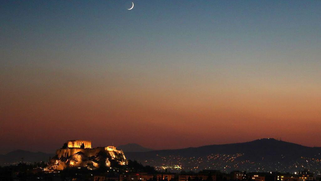 Luna creciente detrás del templo iluminado del Partenón en Atenas