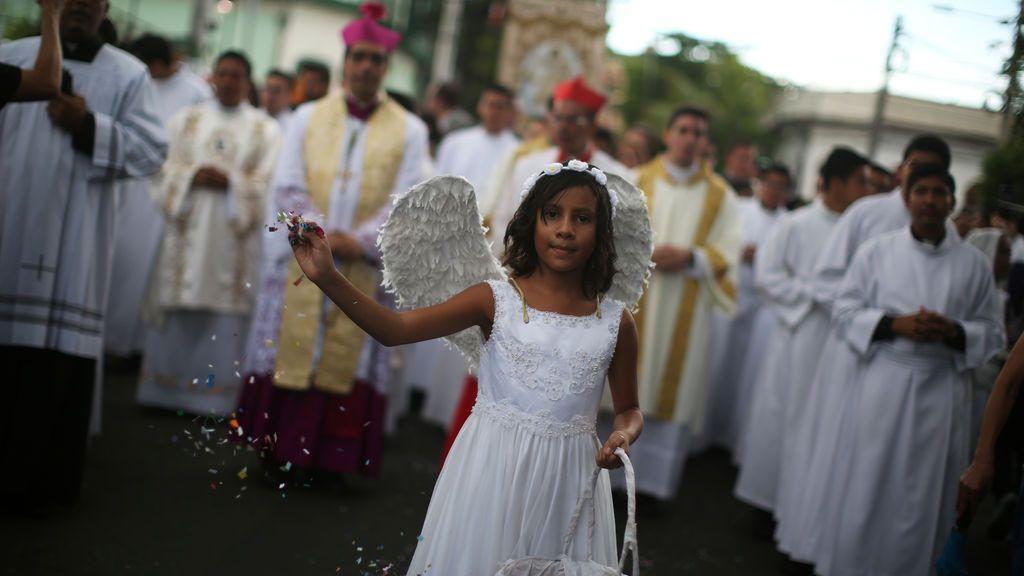 Chica lanza confeti durante el Banquete del Salvador del Mundo en San Salvador