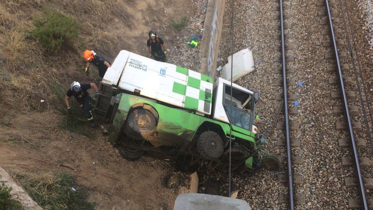 Dos heridos graves tras caerse un camión de Medio Ambiente a las vías del tren en Madrid