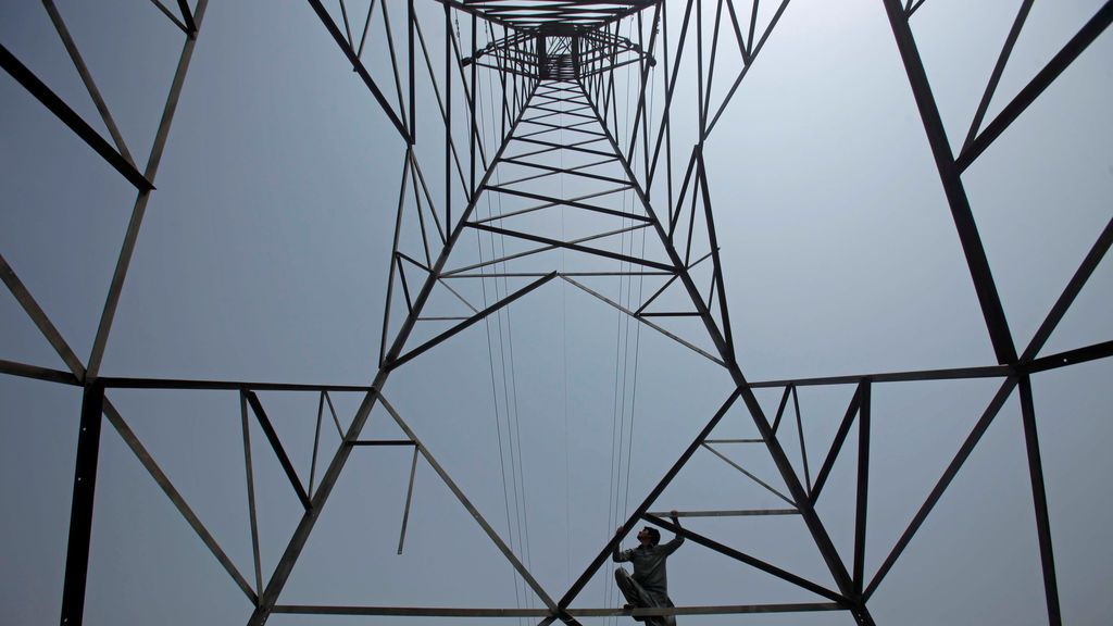 Un hombre escala una torre de alta tensión en Peshawar, Pakistán