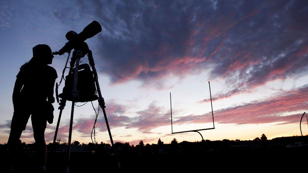 Una mujer mira por el telescopio antes de que se produzca el eclipse solar en Mandras
