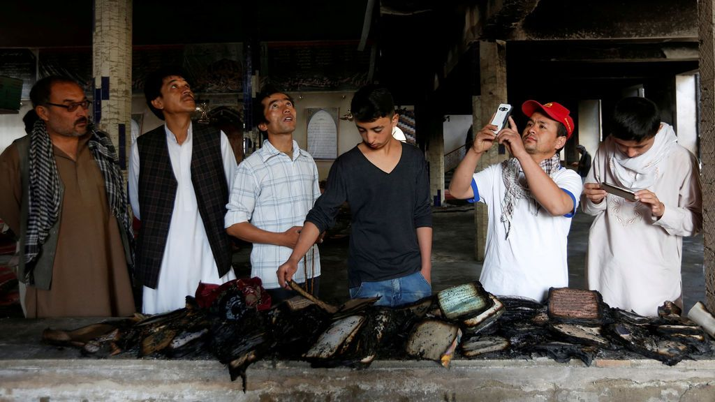 Varios hombres inspeccionan libros del Corán quemados en una mezquita después del ataque en Kabul