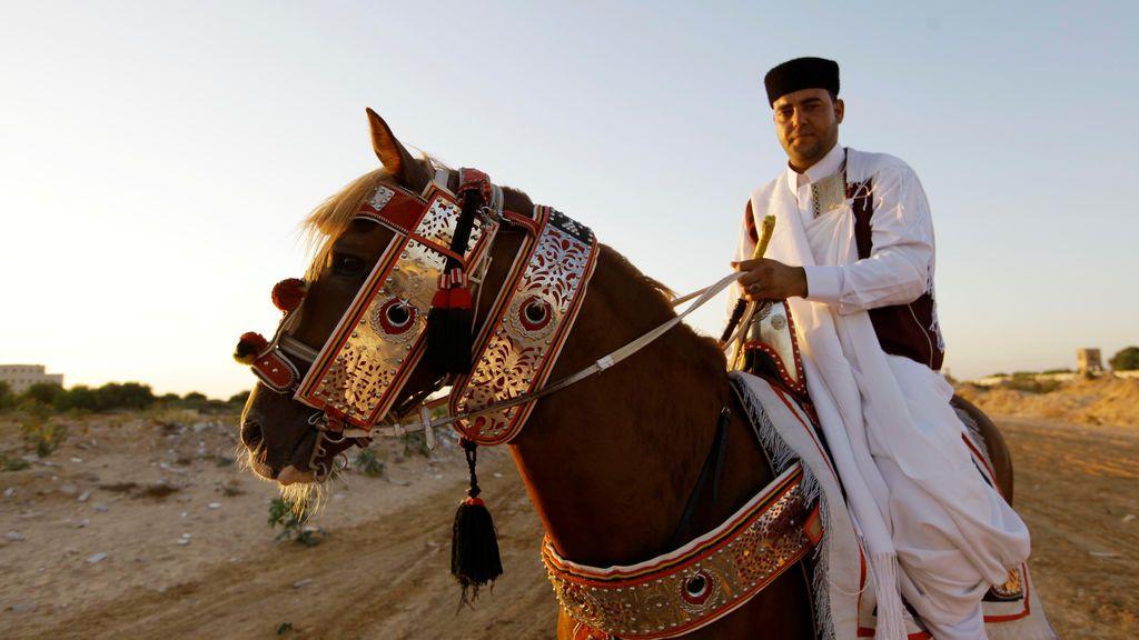 Un hombre libio monta a un caballo vestido con la indumentaria tradicional