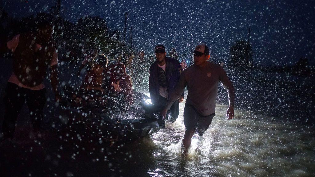 Voluntarios ayudan a empujar una barca con evacuados durante la tormenta tropical Harvey