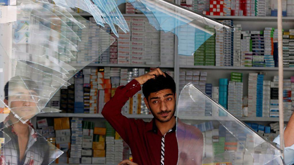 Un tendero afgano reacciona al ver la ventana de su negocio rota tras un ataque suicida en Kabul, Afganistán