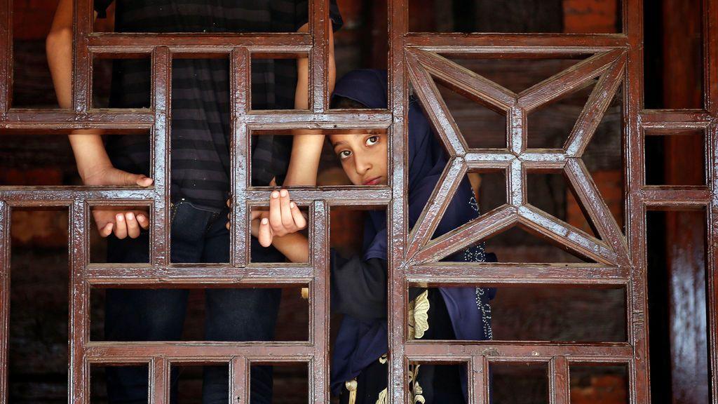 Una niña musulmana mira a través de una ventana durante un festival religioso en Srinagar
