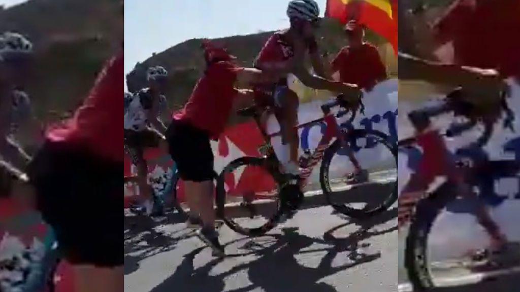 Un aficionado tira al suelo de un empujón a un ciclista en plena carrera de La Vuelta
