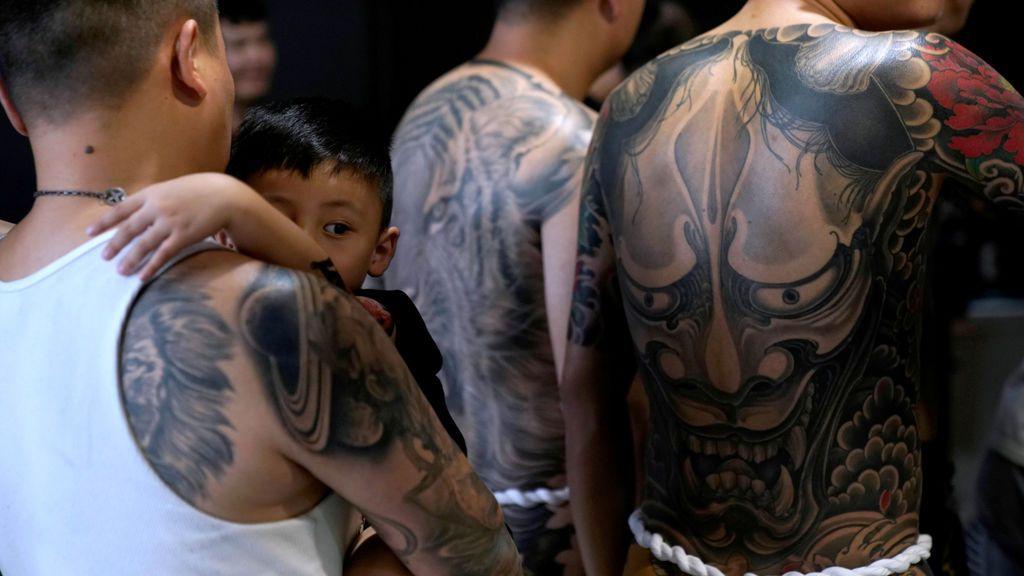 Un padre coge a su hijo en la exposición de tatuajes extremos y arte corporal en Shangai