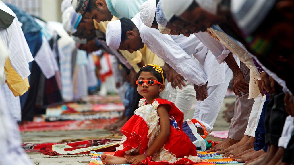 Una niña mira a los musulmanes durante sus plegarias durante el festival Fid al-Adha
