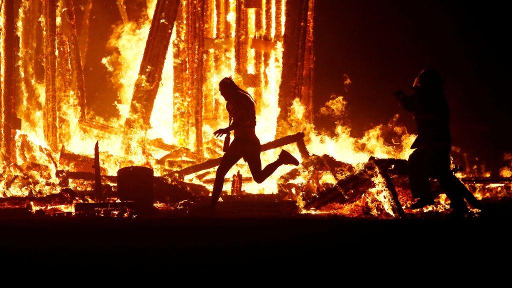 Un participante del festival 'Burning Man' corre hacia el centro de las flamas
