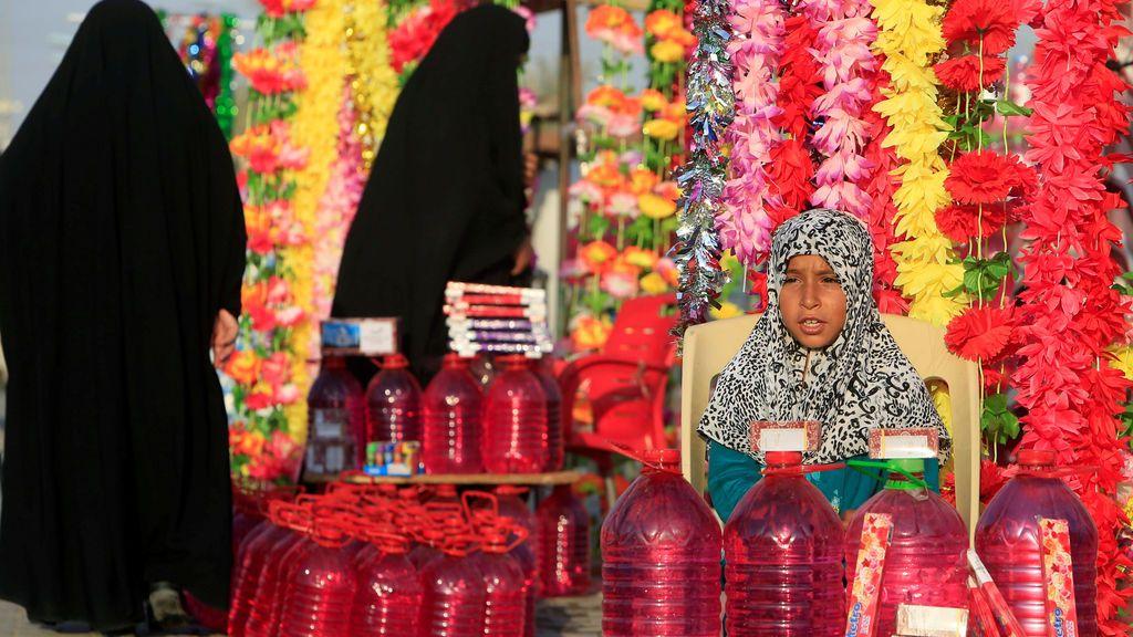 Una chica vende agua y flores en el cementerio 'Valle de la Paz' durante el festival musulmán de Eid al-Adha en Najaf