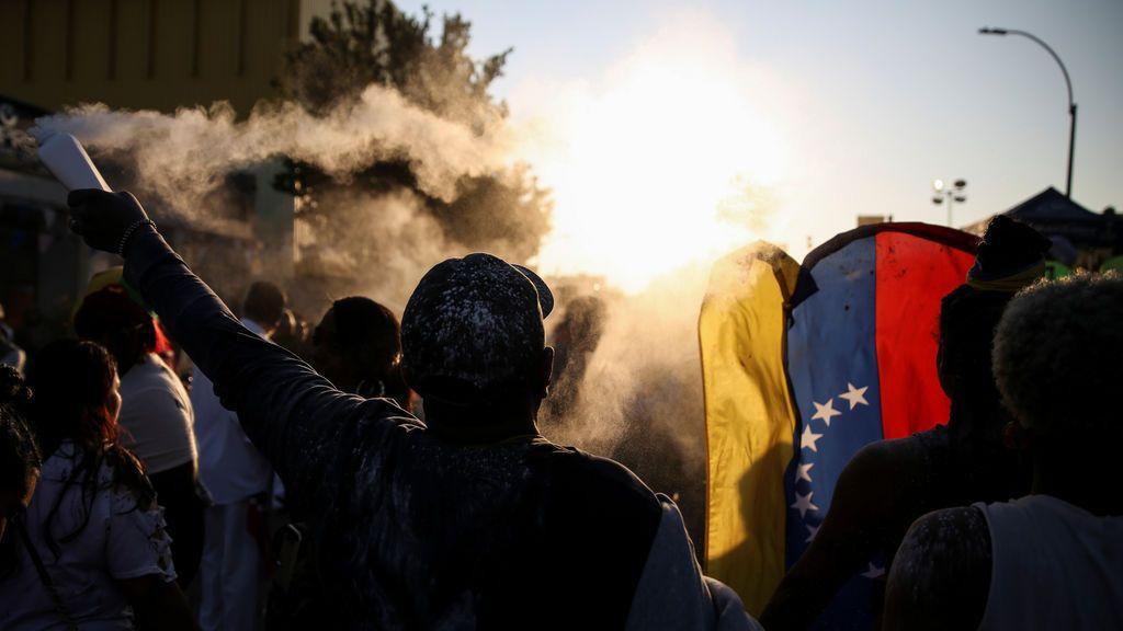 Un participante del Desfile del Día de las Indias Occidentales lanza polvo sobre la multitud