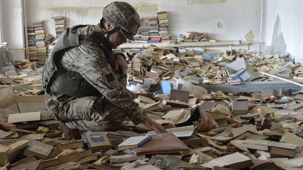 Un soldado ucraniano coge un libro en una biblioteca abandonada