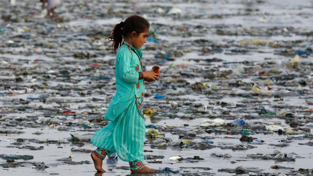 Una niña camina a través de basura depositada por las olas del mar a lo largo de la playa de Clifton en Karachi, Pakistán