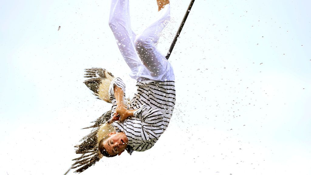 Un hombre tira del cuello de un ganso muerto mientras cae al agua