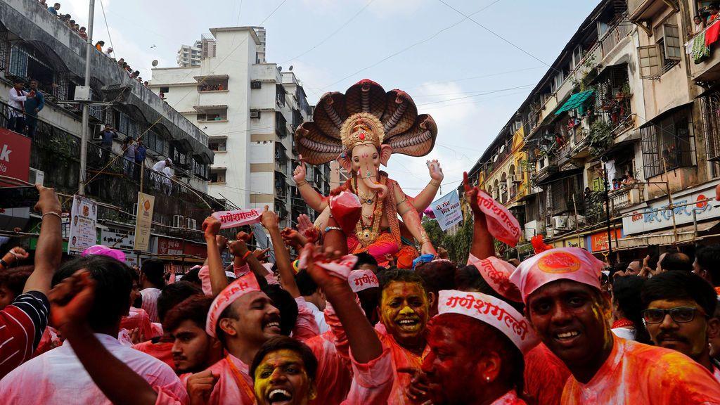 Devotos bailan mientras llevan el ídolo del dios hindú Ganesh