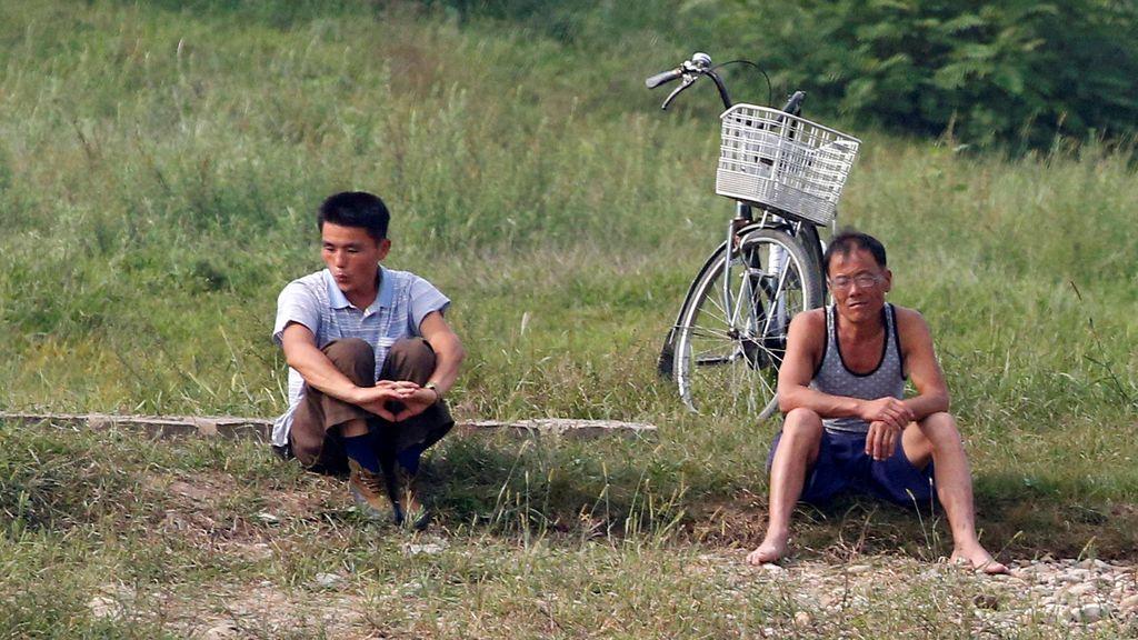 Hombres norcoreanos se encuentran sentados en un banco en el Río Yalu