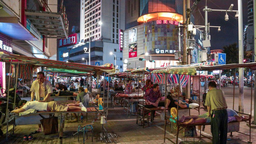 Masajistas ciegos trabajan fuera de los salones de masajes por la noche en China.