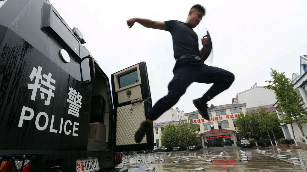 Un policía salta fuera de la furgoneta durante una sesión de entrenamiento en China